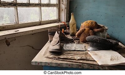 Chernobyl zone, Ukraine. Visit to Pripyat Ghost Town - 4K. table, boots, soft toy cheburashka, hat are on the table by the old window 2020