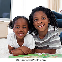 Cherrful siblings reading lying on the floor in the living room