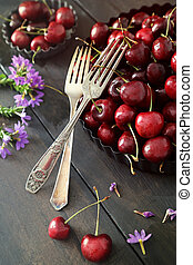Cherries and flowers on old wood table