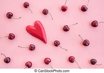 Cherries and red wooden heart on pink canvas
