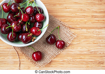 Cherries in a bowl on wooden background