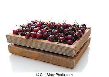 A wooden crate filled with freshly picked cherries. Horizontal format on a white background with reflection.