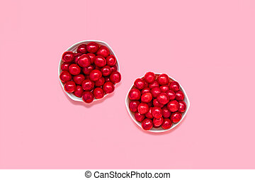 Cherry berries in two bowls on a pink background. Summer concept. Flat lay