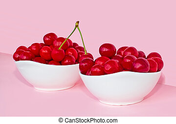 Cherry berries in two bowls on a pink background. Summer concept.