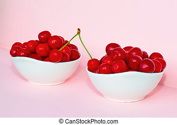 Cherry berries in two bowls on a pink background. Two cherries in one branch - one in one bowl, the second on the other. Two cherries on a branch connect two bowls. Summer concept