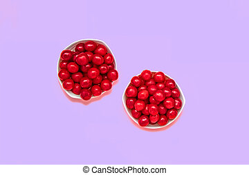 Cherry berries in two bowls on a purple background. Summer concept. Flat lay