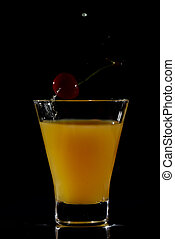 Cherry dropping into orange drink