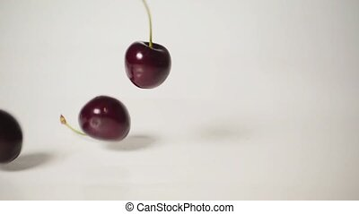 Cherry falls on the table, slow motion