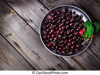 Cherry in metal bowl on old wooden background.
