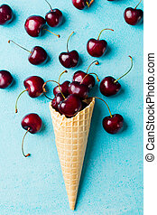 Cherry in waffle cones on blue background Top view