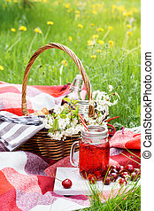 Cherry juice in a jar and wicker picnic basket with food.