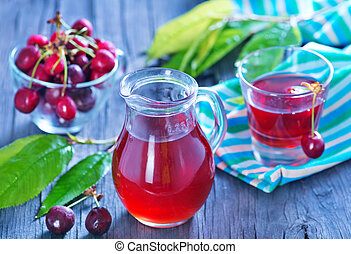 cherry juice in glass jug and on a table