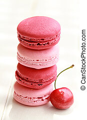 Row of four pink macarons on a white table with fresh fruits