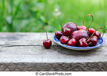Cherry on blue plate close up on the old wooden table, green nature background