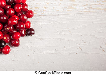 Cherry on white wooden background with copyspace