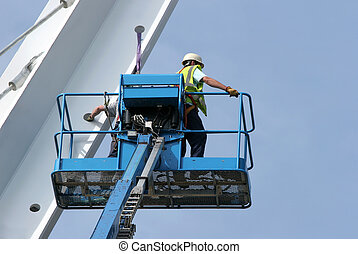 Blue metal cherry picker with workers partially in view, working on a small section of a bridge girder, set against a blue sky.