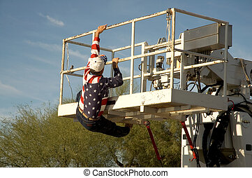 Workman in flag shirt climbing into the bucket of a cherry picker.