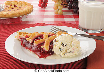 A slice of cherry pie with chocolate chip ice cream and milk