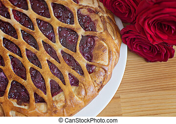Cherry pie and beautiful roses next to it on a table