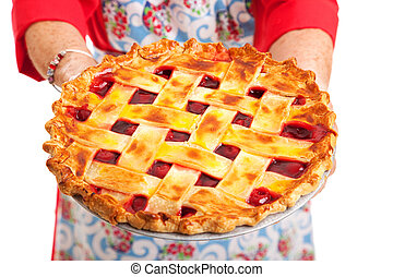Closeup of a homemade cherry pie being held by a stereotypical grandma. Isolated on white.