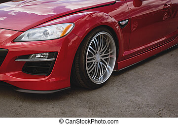 Cherry red car front detail with big light-alloy wheel