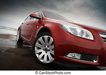 Cherry red car front detail with big light alloy wheel