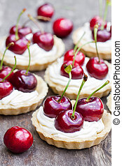 Cherry  tartlets on rustic wooden background