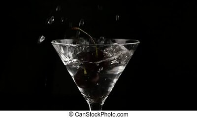 cherry thrown into a glass with alcohol cocktail on a dark...