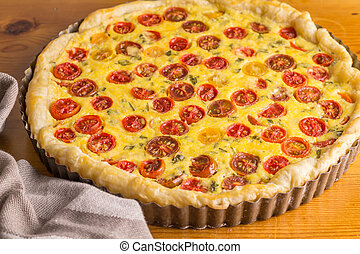 Cherry tomato and egg tart in tin out of on wooden table