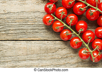Cherry tomato on a branch on a wooden rustic copy space background