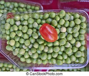 cherry tomato on green peas closeup