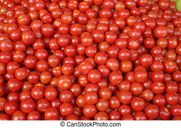 A lot of small, red, shiny cherry tomatoes.