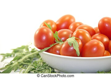 Cherry tomatoes and green fresh rocket on white background