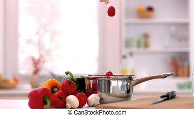 Cherry tomatoes and mushrooms falling in saucepan in kitchen...