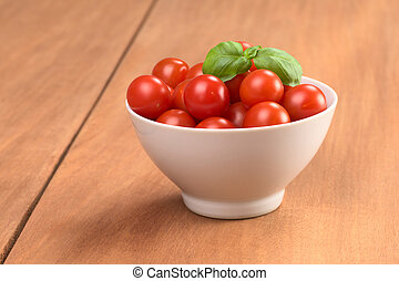 Cherry tomatoes garnished with basil leaf in small white bowl on wood
