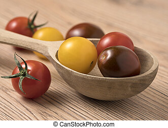 Cherry tomatoes in a variety of colors in wooden spoon.