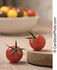 Cherry tomatoes in a variety of colors on a wooden table.