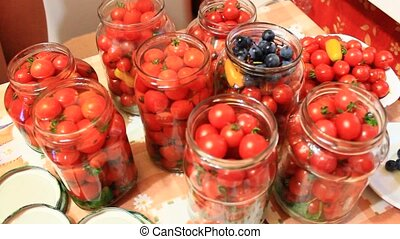 small red cherry tomatos in jars prepared for preservation