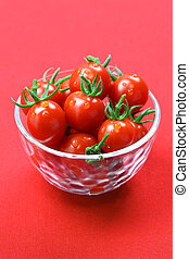 cherry tomatoes in glass bowl isolated on red background, lycopene image