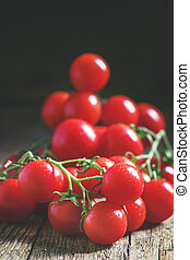 Cherry tomatoes on the vine, vintage wooden background, selective focus, shallow depth of field