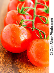 Cherry tomatoes on wooden background close up