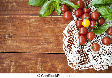 Cherry tomatoes with basil on wooden table