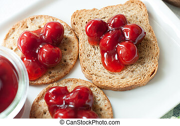 cherry topping dessert on cracker bread white plate