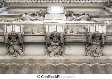 Cherubs sculptures in old stone wall