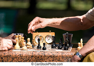 Chess board and hands of people in details