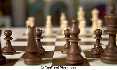 Chess board moves the camera to the left side focused on checkers, ivory chess and brown