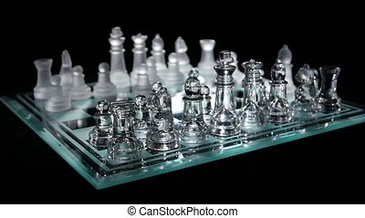 Chess board with chess pieces isolated on black.  Slow motion