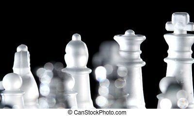 Chess game made of glass. Black background. Close up