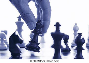 Chess game make your move blue tone close up of hand and...