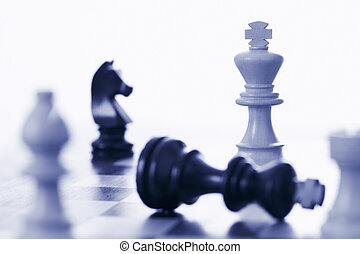 Chess game white king defeating black king blue tone